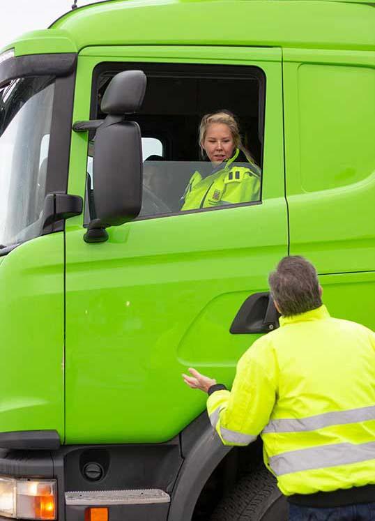 Instruktör talar med tjej i lastbilshytt